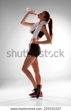 Studio fitness portrait of athletic girl drinks water isolated on white background - stock photo