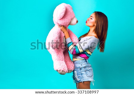 Studio funny portrait of pretty  woman playing with big fluffy teddy bear, mint background, sweet pastel colors. holding her present and sending kiss, making funny face, holidays, joy, childhood. - stock photo