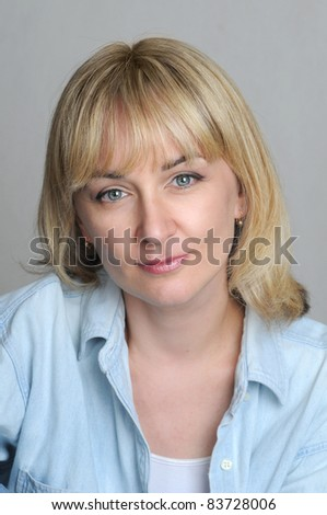 Studio head shot of mid age woman with light smile - stock photo
