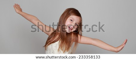 Studio image of a cheerful emotional little girl in a beautiful dress is dancing and having fun on a gray background - stock photo