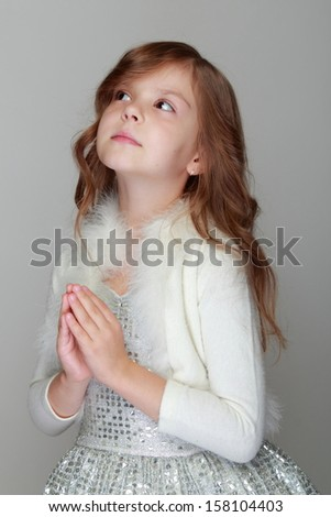 Studio image of a cute little girl holds hands in prayer on a gray background - stock photo