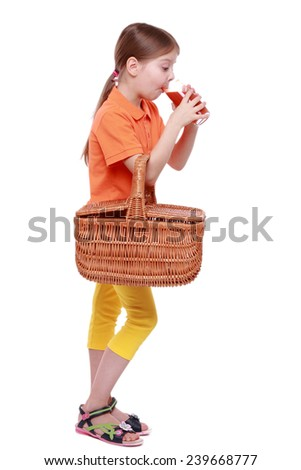 studio image of adorable little girl holding picnic basket and drinking red tomato juice - stock photo
