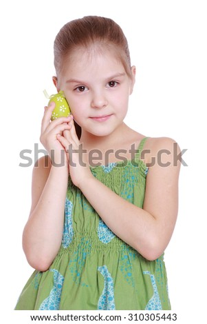 Studio image of cute smiling little girl in a green dress is holding easter eggs isolated on white - stock photo