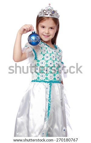 Studio image of emotional lovely little girl in a beautiful dress and a crown holding a Christmas decoration - stock photo