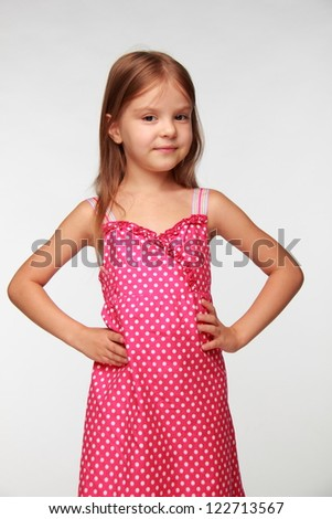 Studio image of lovely little girl wearing summer dress over gray background on Beauty and Fashion theme - stock photo