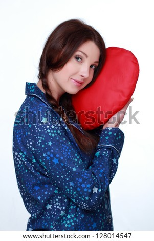 Studio image of sleeping romantic woman with red heart-shaped pillow on white background on Holiday theme - stock photo