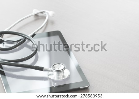studio macro of a stethoscope and digital tablet on wood table background copy space - stock photo