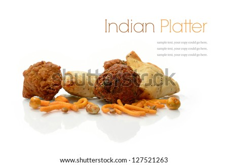 Studio macro of delicious Indian snacks, vegetable samosas, vegetable pakoras and onion bhajis on a white background. Copy space. - stock photo