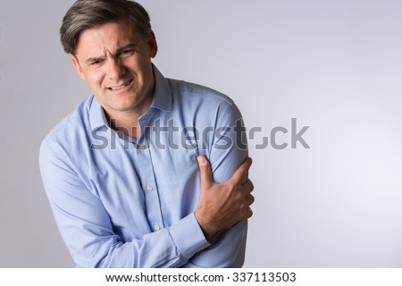 Studio Of Mature Man Clutching Arm As Warning Of Heart Attack - stock photo