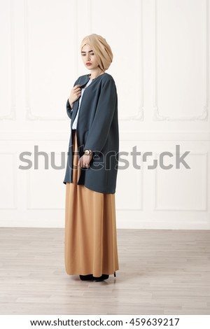 Studio photo girl Caucasoid appearance in a closed, modern Muslim clothes with a turban on his head, on a white background - stock photo