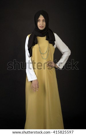 Studio photo of a beautiful young woman eastern type full-length, on a dark background, dressed in the Muslim style - stock photo