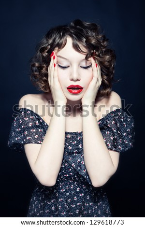 Studio photo of a young woman in a cocktail dress - stock photo