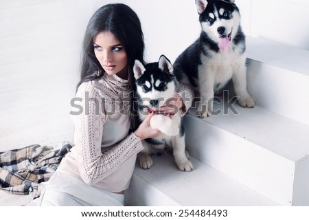 Studio photo of beautiful sexy brunette women with long straight hair wearing in cream sweater, white trousers and necklace relaxing at home and holding a cute little dogs of Husky - stock photo