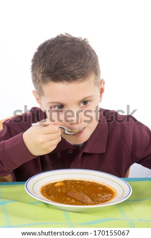 Studio photograph of a child eating a delicious lentil stew with potatoes and sausage - stock photo