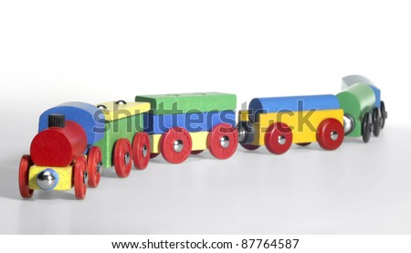 studio photography of a colorful wooden toy train in light back - stock photo