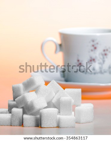 Studio photography of a lump sugar pile and porcelain coffee cup and saucer in light orange back - stock photo