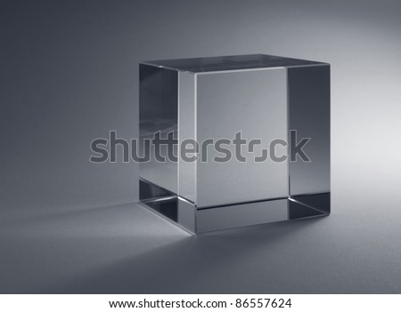 studio photography of a solid glass cube in grey back - stock photo
