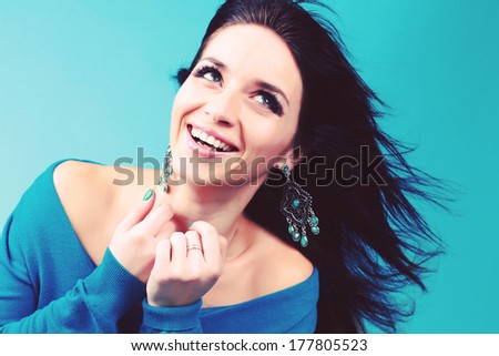 Studio photography. Portrait of a beautiful brunette with flowing hair. Flawless white smile. - stock photo