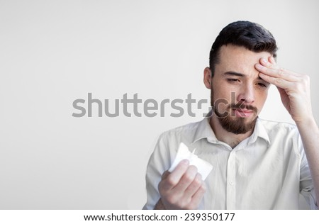 studio picture from a young man with handkerchief. Sick guy isolated has runny nose. - stock photo
