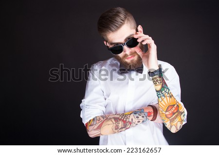 studio portarit of  ayoung fashionable hipster man in white shirt posing over a black background - stock photo