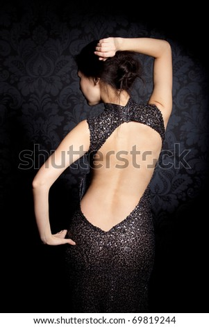 Studio portrait of a beautiful lady in a black dress - stock photo