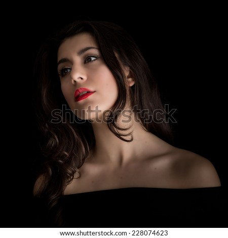 Studio portrait of a beautiful sensual young brunette woman with long hair wearing make-up and red lipstick staring dreamily off camera isolated against a black background - stock photo
