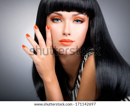 Studio portrait of a beautiful woman with red nails, glamour makeup and long black hair. - stock photo