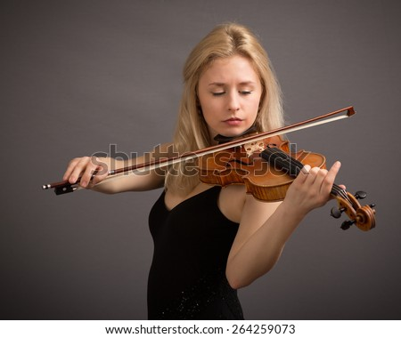 Studio portrait of a beautiful young blond female violin player playing a lovely tune isolated against a dark grey background. - stock photo