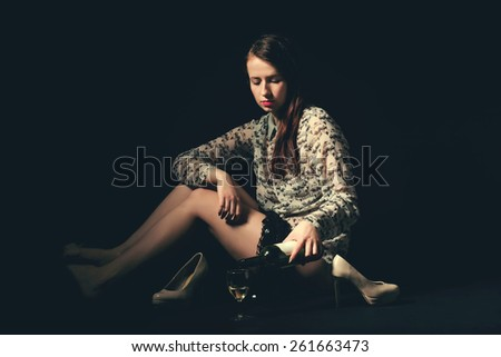 Studio portrait of a beautiful young brunette woman holding a bottle of white wine in retro colors - stock photo