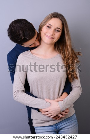 studio portrait of a beautiful young couple man and woman love standing against blue gray background - stock photo