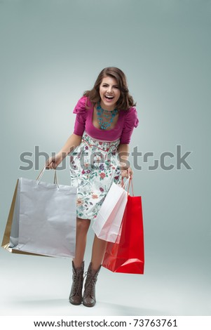 studio portrait of a beautiful young woman, in a colourful outfit, holding in her hands a few shopping bags. she is laughing and looking very happy. - stock photo