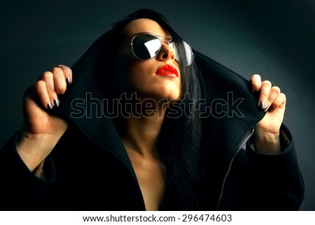 Studio portrait of a beautiful young woman in black coat - stock photo