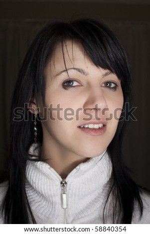 Studio portrait of a beautiful young woman with a white jumper. - stock photo