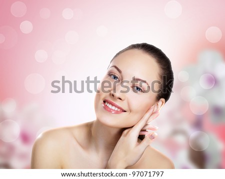 Studio portrait of a beautiful young woman with flowers on background - stock photo