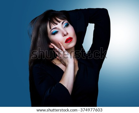 studio portrait of a brunette model with long hair and bright makeup - stock photo