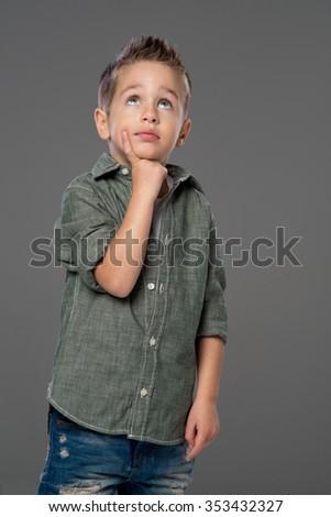 Studio portrait of a child thinking, gray background  - stock photo