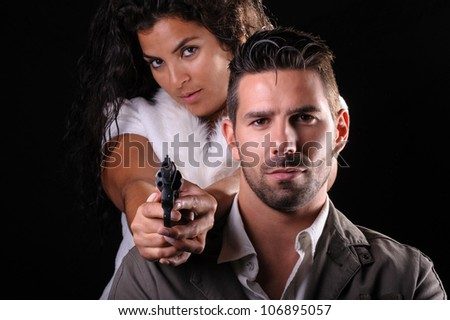 studio portrait of a couple of criminals or detectives with a gun - stock photo