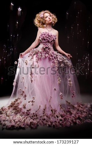 Studio portrait of a girl in a dress of cherry blossoms - stock photo