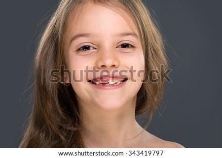 Studio portrait of a girl. She smiles and shows a fallen baby tooth?.  Isolated on gray - stock photo