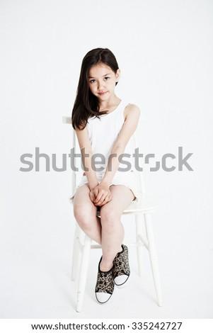 Studio portrait of a girl sitting. Light background - stock photo