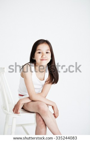 Studio portrait of a girl smiling. Light background - stock photo