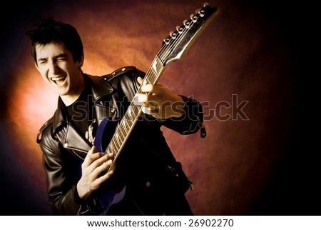 studio portrait of a happy young excited man playing a guitar - stock photo