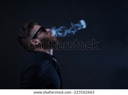 studio portrait of a hipster man smoking with black background - stock photo