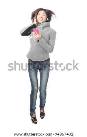 Studio portrait of a jumping girl in headphones listen music isolated on white background, model is a asian beauty - stock photo