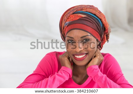 Studio portrait of a mature African happy woman  wearing   headscarf  - stock photo