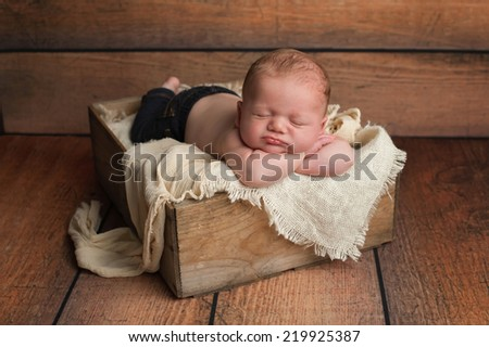 Studio portrait of a 1 month old newborn baby boy wearing jeans and sleeping in a vintage wooden crate. - stock photo