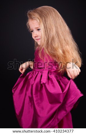 Studio portrait of a pretty little girl in a pink dress on a black background - stock photo