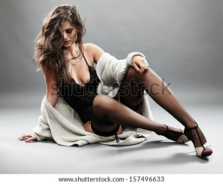 Studio portrait of a sexy brunette in black lingerie, stockings and cardigan over grey background - stock photo