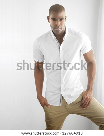 Studio portrait of a sexy male fashion model in stylish casual clothing against white with copy space - stock photo