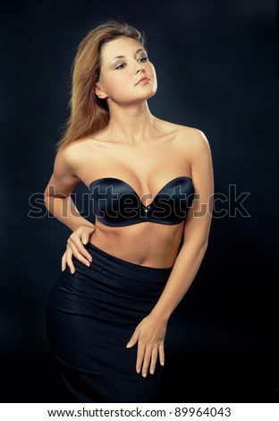 studio portrait of a sexy petite curvy woman, isolated against black background - stock photo